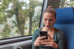 Κατάπληκτη γυναίκα που ελέγχει το smartphone στην οδό μετά από να λάβει συγκλονίζοντας ειδήσεις σε ένα ταξίδι τραίνων στοκ φωτογραφία