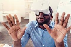 Κατάπληκτος νεαρός άνδρας που απολαμβάνει τα γυαλιά εικονικής πραγματικότητας Στοκ εικόνα με δικαίωμα ελεύθερης χρήσης