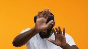 Κατάπληκτο αφρικανικό αρσενικό που φορά την κάσκα εικονικής πραγματικότητας, τρισδιάστατη ψυχαγωγία προσομοίωσης απόθεμα βίντεο