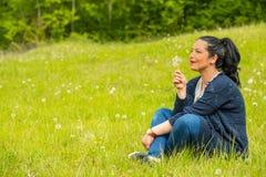 Κατάπληκτες φυσώντας πικραλίδες γυναικών Στοκ εικόνα με δικαίωμα ελεύθερης χρήσης