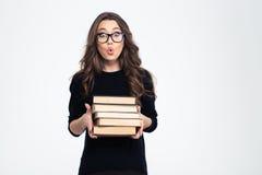 Κατάπληκτη γυναίκα στα γυαλιά που κρατά τα βιβλία Στοκ εικόνες με δικαίωμα ελεύθερης χρήσης