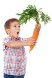 Κατάπληκτο αγόρι με το μεγάλο καρότο Στοκ εικόνα με δικαίωμα ελεύθερης χρήσης