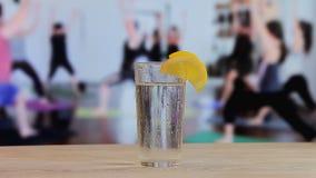 Κατάρτιση γιόγκας, pilates, γυαλί με το νερό και λεμόνι απόθεμα βίντεο