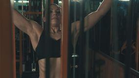Κατάρτιση γυναικών με την βάρος-ανύψωση της μηχανής κατάρτισης σε σε αργή κίνηση στη σκοτεινή γυμναστική φιλμ μικρού μήκους