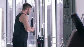 Κατάρτιση δύναμης, ισχυρός αθλητικός τύπος που κάνει το μυ που στηρίζεται workout στον προσομοιωτή έλξης εργαζόμενος στο σώμα στο απόθεμα βίντεο