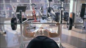 Κατάρτιση δύναμης, ισχυρό μυϊκό bodybuilder που κάνει τον Τύπο πάγκων με το barbell ενώ αθλητική δύναμη workout στη γυμναστική απόθεμα βίντεο