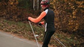 Κατάρτιση ενός αθλητή στους σκέιτερ κυλίνδρων Ο γύρος Biathlon στον κύλινδρο κάνει σκι με τους πόλους σκι, στο κράνος Φθινόπωρο φιλμ μικρού μήκους