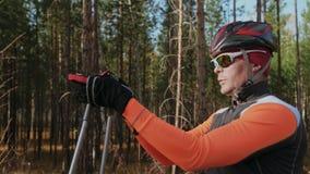 Κατάρτιση ενός αθλητή στους σκέιτερ κυλίνδρων Ο γύρος Biathlon στον κύλινδρο κάνει σκι με τους πόλους σκι, στο κράνος Φθινόπωρο απόθεμα βίντεο