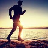 Κατάρτιση στο ηλιοβασίλεμα Μια σκιαγραφία του jogger στην πορεία κατά μήκος της ακτής λιμνών Στοκ Φωτογραφία