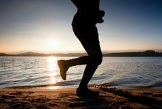 Κατάρτιση στο ηλιοβασίλεμα Μια σκιαγραφία του jogger στην πορεία κατά μήκος της ακτής λιμνών Στοκ Εικόνες