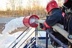 Κατάρτιση των πυροσβεστών Ο πυροσβέστης εξαφανίζει την πυρκαγιά με τον αφρό Στοκ Εικόνες