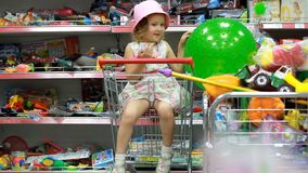 Κατάστημα παιδιών ` s με τα παιχνίδια Ένα παιδί σε μια υπεραγορά κάθεται στο κάρρο αγορών απόθεμα βίντεο