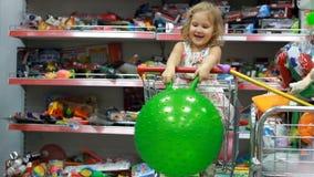 Κατάστημα παιδιών ` s με τα παιχνίδια Ένα παιδί σε μια υπεραγορά κάθεται στο κάρρο αγορών φιλμ μικρού μήκους