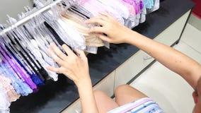 Κατάστημα του εσώρουχου γυναικών ` s Κιλότες γυναικών ` s στις κρεμάστρες σε ένα κατάστημα φύλων, 4k, σε αργή κίνηση απόθεμα βίντεο