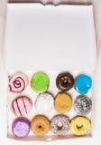 Κατάταξη των διάφορων ζωηρόχρωμων donuts σε ένα κιβώτιο της Λευκής Βίβλου, τοπ άποψη Στοκ εικόνα με δικαίωμα ελεύθερης χρήσης