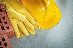 Κατάταξη των κόκκινων γαντιών ασφάλειας καπέλων τούβλων σκληρών στη συγκεκριμένη πλάτη Στοκ Εικόνες