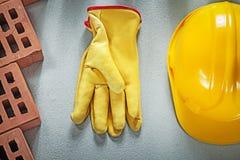 Κατάταξη των κόκκινων προστατευτικών γαντιών καπέλων τούβλων σκληρών στο σκυρόδεμα Στοκ φωτογραφία με δικαίωμα ελεύθερης χρήσης