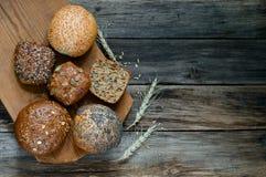 Κατάταξη των ρόλων ψωμιού πολυ-σιταριού επάνω στον παλαιό ξύλινο πίνακα Στοκ Φωτογραφίες