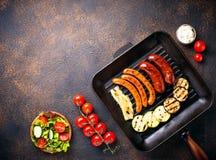 Κατάταξη των ψημένων στη σχάρα λουκάνικων και των λαχανικών στο τηγάνι σχαρών Στοκ φωτογραφίες με δικαίωμα ελεύθερης χρήσης