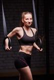 Κατάλληλα νέα φίλαθλα gymnast εκμετάλλευσης γυναικών δαχτυλίδια και χαμόγελο στη διαγώνια κατάλληλη γυμναστική ενάντια στο τουβλό Στοκ Εικόνα