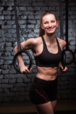Κατάλληλα νέα φίλαθλα gymnast εκμετάλλευσης γυναικών δαχτυλίδια και χαμόγελο στη διαγώνια κατάλληλη γυμναστική ενάντια στο τουβλό Στοκ εικόνες με δικαίωμα ελεύθερης χρήσης