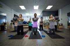 Κατάλληλες γυναίκες που εκτελούν την τεντώνοντας άσκηση με τη σφαίρα ικανότητας στη γυμναστική Στοκ φωτογραφία με δικαίωμα ελεύθερης χρήσης