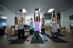 Κατάλληλες γυναίκες που εκτελούν την τεντώνοντας άσκηση με τη σφαίρα ικανότητας στη γυμναστική Στοκ εικόνα με δικαίωμα ελεύθερης χρήσης