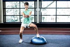 Κατάλληλη γυναίκα που κάνει την άσκηση με τη σφαίρα bosu Στοκ Εικόνες