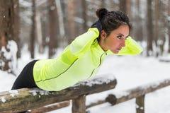 Κατάλληλη γυναίκα που κάνει την πίσω άσκηση επέκτασης υπαίθρια στα ξύλα Θηλυκό πάρκο αθλητικού πρότυπο ασκώντας υπαίθριο χειμώνα στοκ εικόνες
