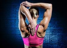 Κατάλληλη γυναίκα που κάνει την τεντώνοντας άσκηση στο μπλε κλίμα τοίχων Στοκ Εικόνες