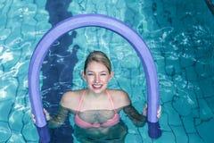 Κατάλληλη γυναίκα που κάνει τη αερόμπικ aqua με τους κυλίνδρους αφρού Στοκ Φωτογραφίες