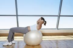 Κατάλληλη γυναίκα που κάνει το κάθομαι-UPS στη σφαίρα άσκησης Στοκ εικόνες με δικαίωμα ελεύθερης χρήσης