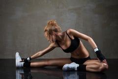 Κατάλληλη γυναίκα που τεντώνει το πόδι της πέρα από το σκοτεινό υπόβαθρο στοκ εικόνα με δικαίωμα ελεύθερης χρήσης