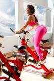 Κατάλληλη γυναίκα στο ποδήλατο άσκησης στη γυμναστική Στοκ Εικόνα