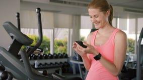 Κατάλληλη ενεργός αθλητική γυναίκα που κάνει τις ασκήσεις στο velosimulator Χρησιμοποίηση του smartphone της, μήνυμα με το φίλο απόθεμα βίντεο
