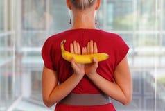 Κατάλληλη επιχειρησιακή γυναίκα με την μπανάνα ως healhy πρόχειρο φαγητό στοκ φωτογραφίες