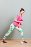 Κατάλληλη και φίλαθλη γυναίκα που κάνει το αεροβικό workout με τους αλτήρες στοκ εικόνα με δικαίωμα ελεύθερης χρήσης