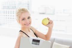 Κατάλληλη κλίμακα και μήλο εκμετάλλευσης γυναικών στο στούντιο ικανότητας Στοκ φωτογραφία με δικαίωμα ελεύθερης χρήσης