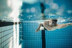 Κατάλληλη νέα αρσενική κατάρτιση κολυμβητών στη λίμνη στοκ εικόνες