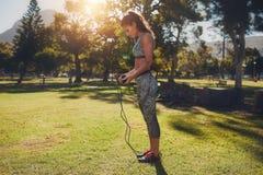 Κατάλληλη νέα γυναίκα με το πηδώντας σχοινί υπαίθρια στο πάρκο Στοκ Εικόνα