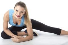 Κατάλληλη νέα γυναίκα που κάνει τις τεντώνοντας ασκήσεις πατωμάτων Στοκ εικόνα με δικαίωμα ελεύθερης χρήσης