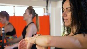 Κατάλληλη νέα γυναίκα που τρέχει και που ελέγχει το σφυγμό στο smartwatch κατά τη διάρκεια του workout στη λέσχη ικανότητας απόθεμα βίντεο