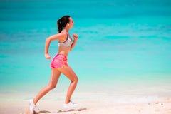 Κατάλληλη νέα γυναίκα που τρέχει κατά μήκος της τροπικής παραλίας sportswear της στοκ φωτογραφίες με δικαίωμα ελεύθερης χρήσης