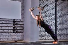 Κατάλληλη νέα γυναίκα στη μαύρη sportwear άσκηση με τα γυμναστικά δαχτυλίδια στη γυμναστική ενάντια στο τουβλότοιχο Στοκ φωτογραφία με δικαίωμα ελεύθερης χρήσης