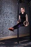 Κατάλληλη νέα γυναίκα στη μαύρη sportwear άσκηση με τα γυμναστικά δαχτυλίδια στη γυμναστική ενάντια στο τουβλότοιχο Στοκ Εικόνες