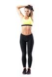 Κατάλληλη όμορφη γυναίκα sportswear στους μυς τεντώματος triceps με το χέρι πίσω από το λαιμό στοκ φωτογραφία