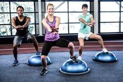Κατάλληλοι άνθρωποι που κάνουν την άσκηση με τη σφαίρα bosu Στοκ Φωτογραφίες