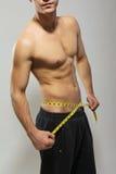Κατάλληλος νεαρός άνδρας γυμνοστήθων που μετρά τη μέση του στοκ εικόνες με δικαίωμα ελεύθερης χρήσης