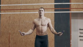 Κατάλληλος νεαρός άνδρας που κάνει τις ασκήσεις σχοινιών άλματος στη γυμναστική απόθεμα βίντεο