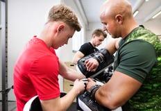 Κατάλληλος νεαρός άνδρας στη γυμναστική με τον εκπαιδευτή του που προετοιμάζεται για τον εγκιβωτισμό Στοκ φωτογραφία με δικαίωμα ελεύθερης χρήσης